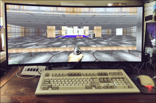 """Doom"" on a widescreen monitor behind a desktop keyboard and mouse."